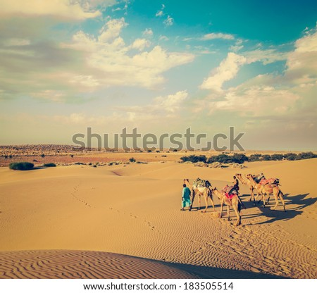 Vintage retro hipster style travel image of Rajasthan travel background - two Indian cameleers (camel drivers) with camels in dunes of Thar desert. Jaisalmer, Rajasthan, India - stock photo