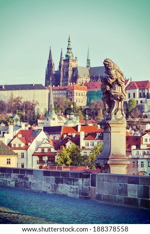 Vintage retro hipster style travel image of statue on Charles Brigde with St. Vitus Cathedral in background in Prague - stock photo
