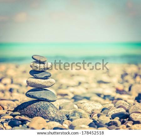 Vintage retro hipster style travel image of Zen meditation background -  balanced stones stack close up on sea beach - stock photo