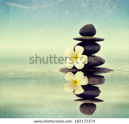 Vintage retro hipster style travel image of Zen spa concept background - Zen massage stones with frangipani plumeria flower in water reflection with grunge texture overlaid - stock photo