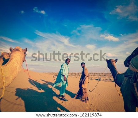 Vintage retro hipster style travel image ofvintage retro hipster style travel image of Rajasthan travel background - two indian cameleers (camel drivers) with camels.  Thar desert,  Rajasthan, India - stock photo