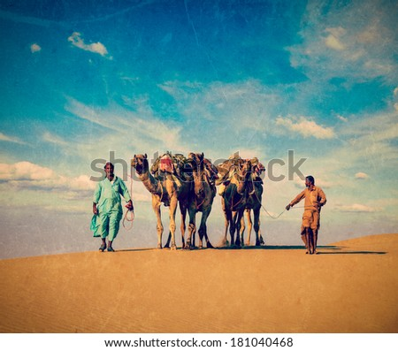 Vintage retro hipster style travel image Rajasthan travel background - two Indian cameleers (camel drivers) with camels in dunes of Thar desert Jaisalmer, Rajasthan, India with grunge texture overlaid - stock photo