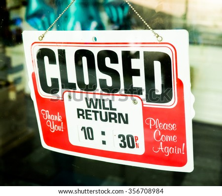 Vintage retro looking Closed sign in a shop showroom with reflections