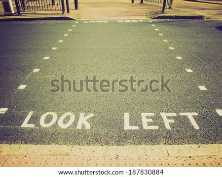 Vintage retro looking Look Left warning at a pedestrian zebra crossing in a London street - stock photo