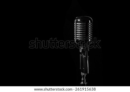 Vintage retro microphone isolated on black background - stock photo