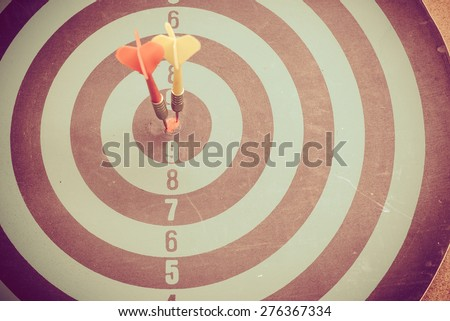 Vintage retro picture style - Dart is an opportunity and Dartboard is the target and goal. So both of that represent a challenge. Bullseye and Dart. - stock photo