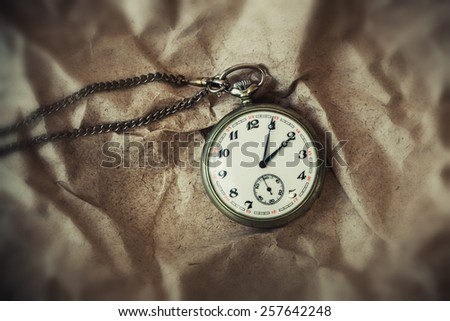vintage retro pocket watch on a chain on a vintage background