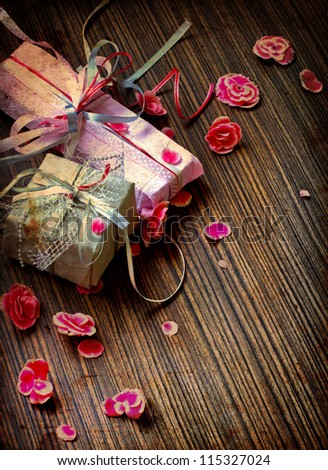 Vintage Retro Present,gift bow with petal from flowers on wooden table/Vintage holiday background/Valentines day background - stock photo