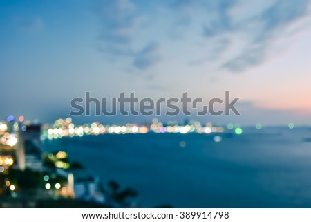 Vintage retro style Blur abstract background cityscape bokeh nightlife illuminated night light on ocean bay beachfront waterscape: Blurry rooftop aerial view of Pattaya city beach seaside twilight sky - stock photo