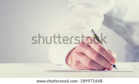 Vintage retro style image of a man signing a document or writing notes on a sheet of paper, close up of his hand with copyspace to the left. - stock photo