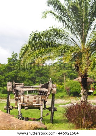 vintage retro style used wood metal cart standing on green grass garden floor in resort hotel in THAILAND new usage as symbolic function decorative object for country home style hotel