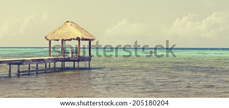 Vintage retro stylized photo of Caribbean turquoise sea with beach hut and clouds in the background, panoramic view - stock photo