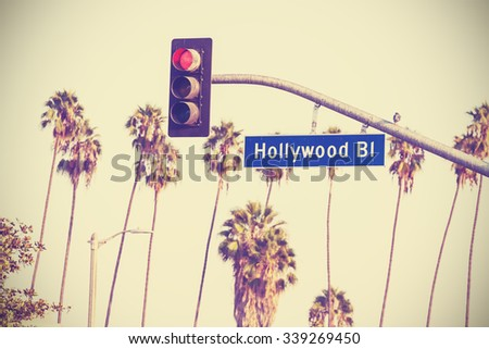Vintage retro toned Hollywood boulevard sign and traffic lights with palm trees in the background, Los Angeles, USA. - stock photo