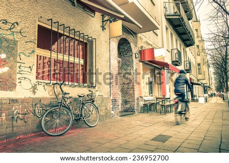 Vintage retro travel postcard of a narrow street in the former east side of Berlin - Mix of past and present in the multicultural capital of Germany - Everyday life with people and bike on the road - stock photo
