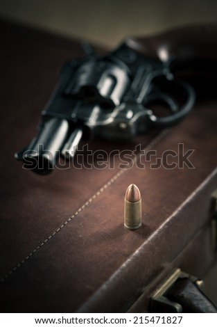 Vintage revolver gun on leather briefcase with bullet close-up.