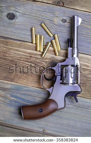 Vintage revolver nagant with a rotating drum and the seven golden cartridges on textured old boards - stock photo