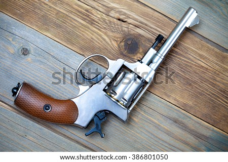 Vintage revolver nagant with a rotating drum on textured old boards - stock photo