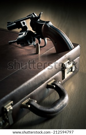 Vintage revolver with cylinder open and bullet on leather briefcase.