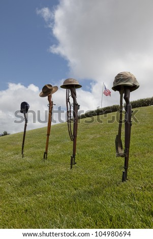 Vintage riflles and soldier's hats and helmets forming Fallen Soldier Battle Crosses, American Flag behind. - stock photo