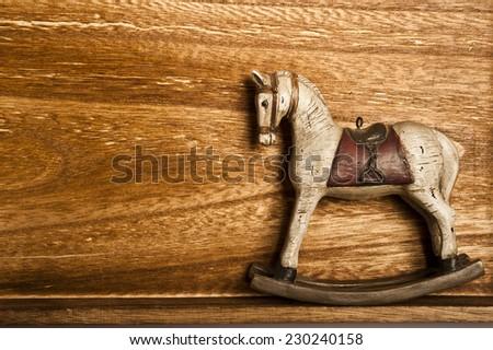vintage rocking horse on wood - stock photo