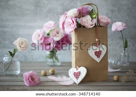 Vintage romantic backgroud with flowers and handcrafted hearts and feathers - stock photo