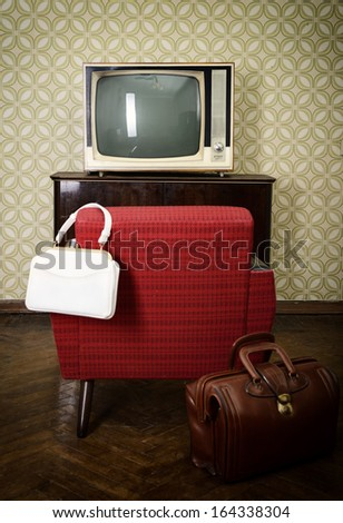 Vintage room with wallpaper, old fashioned armchair, retro tv and two bags. Toned - stock photo
