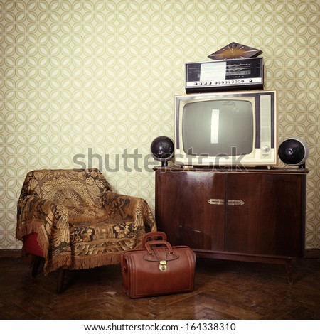 Vintage room with wallpaper, old fashioned armchair, retro tv, bag, clocks, radio player and loudspeakers. Toned - stock photo
