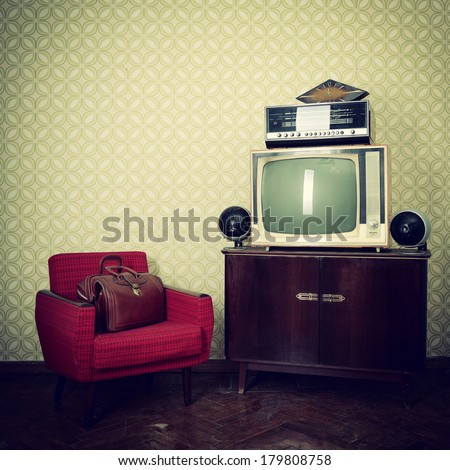 Vintage room with wallpaper, old fashioned armchair, retro tv, bag, clocks, radio player and loudspeakers - stock photo