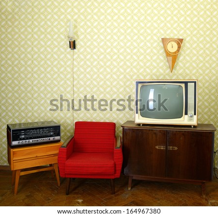 Vintage room with wallpaper, old fashioned armchair, retro tv, clocks, radio player and lamp - stock photo