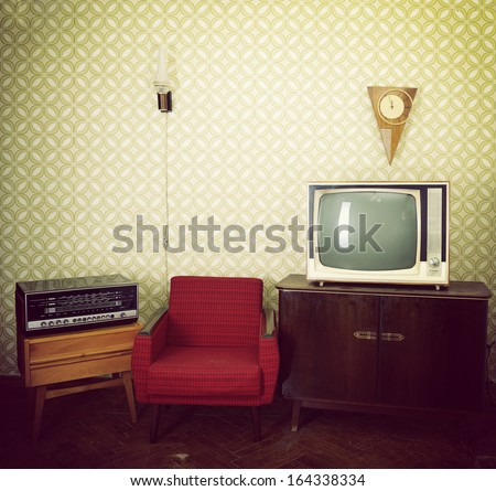 Vintage room with wallpaper, old fashioned armchair, retro tv, clocks, radio player and lamp. Toned - stock photo