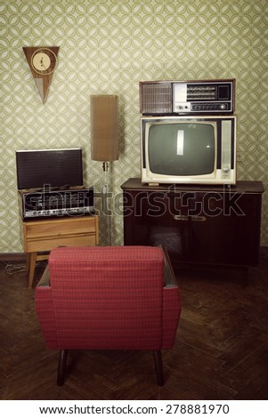 Vintage room with wallpaper, tv, old fashioned armchair, retro player, loudspeakers, clocks and standart lamp, toned - stock photo