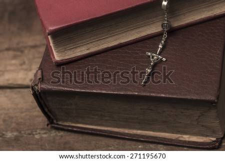 vintage rosary beads on old books - stock photo