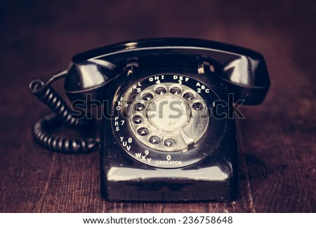 Vintage rotary phone on a rustic farm table with filtered effect - stock photo