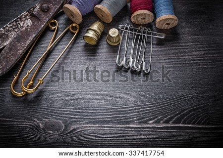 Vintage rough scissors reels of thread thimbles safety pins. - stock photo