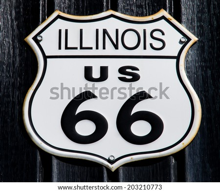 Vintage Route 66 Illinois sign with black wood panels in background.