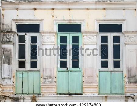 vintage ruin weathered green wooden shutter window on white classic handcraft concrete wall background, old house in Phuket , Thailand