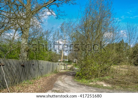 Vintage rural scene in spring, old wooden fence standing at country road - stock photo