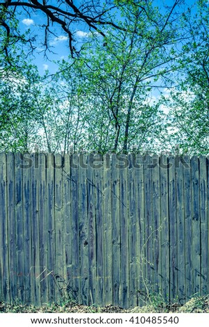 Vintage rural scene with old wooden fence from wooden planks standing at country road - stock photo