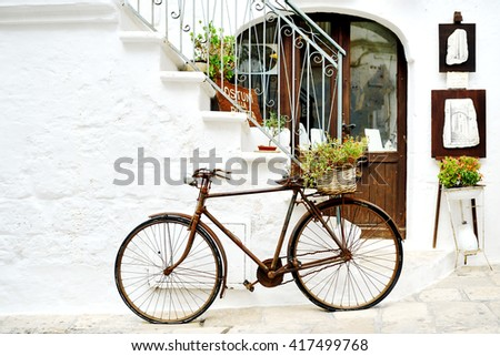 vintage rusty bicycle against a wall in white city Ostuni, Apulia, Italy - artistic picture italian style concept - stock photo