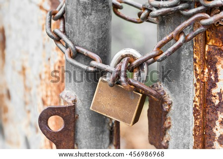 Vintage rusty gate with lock and metal chain - stock photo
