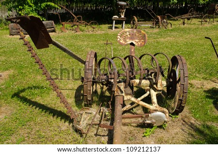 Vintage rusty grass cutting and harvesting agricultural machinery equipment.