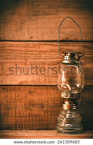vintage rusty oil lamp on wooden background.