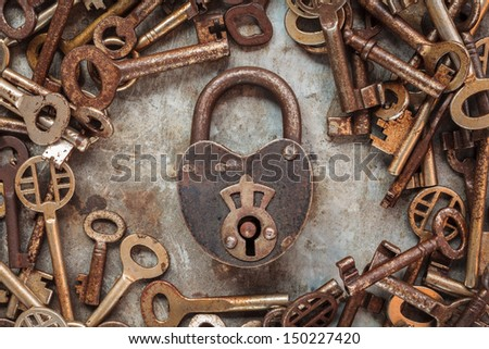 Vintage rusty padlock surrounded by old keys on a weathered steel background - stock photo