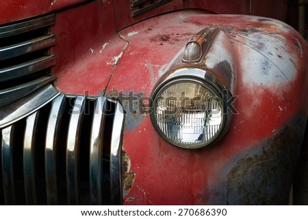 Vintage rusty red truck car with a new headlight, soft focus - stock photo