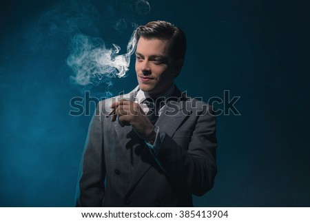 Vintage 1940s business man in suit and tie smoking cigarette against blue wall.