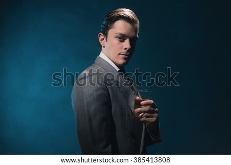 Vintage 1940s fashion man in suit and tie holding glass of whiskey against blue wall. - stock photo