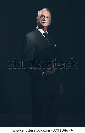 Vintage 40s senior businessman holding hat. Studio shot. - stock photo