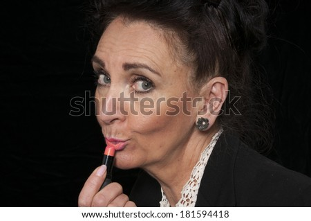 Vintage 1940's style woman applying her lipstick isolated on black background