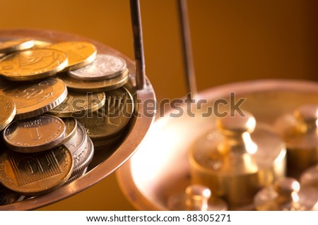 vintage scale wheights outweigh coins on an old balance - stock photo
