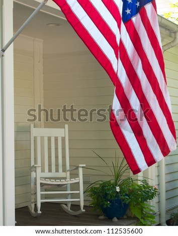 Vintage scene of rocking chair and US flag on front porch - stock photo